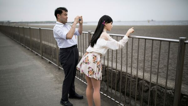 In this picture taken on May 9, 2017, physiotherapist Masayuki Ozaki (L) takes pictures of his silicone sex doll Mayu in Tokyo Bay. - Sputnik International