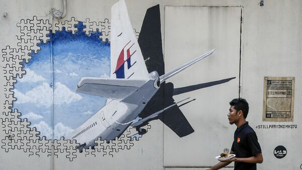 In this Tuesday, Feb. 23, 2016, file photo, a waiter walks past a mural of flight MH370 in Shah Alam outside Kuala Lumpur, Malaysia. - Sputnik International