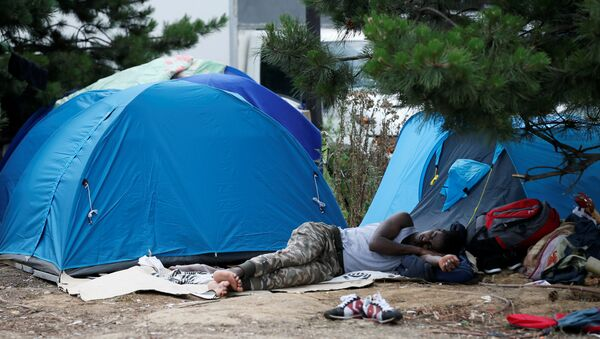 A migrant sleeps next to tents installed in a street near the entrance of the reception center for migrants and refugees at porte de La Chapelle, north of Paris, France, July 6, 2017 - Sputnik International