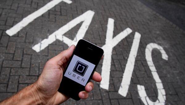 A photo illustration shows the Uber app logo displayed on a mobile telephone. (File) - Sputnik International