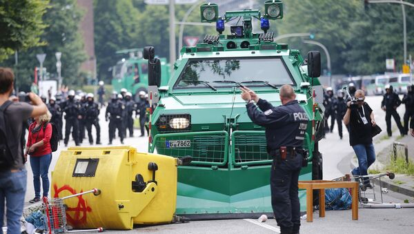 A German policeman stands in front of a barricade left by protesters in front of a police vehicle during the G20 summit in Hamburg, Germany, July 7, 2017 - Sputnik International