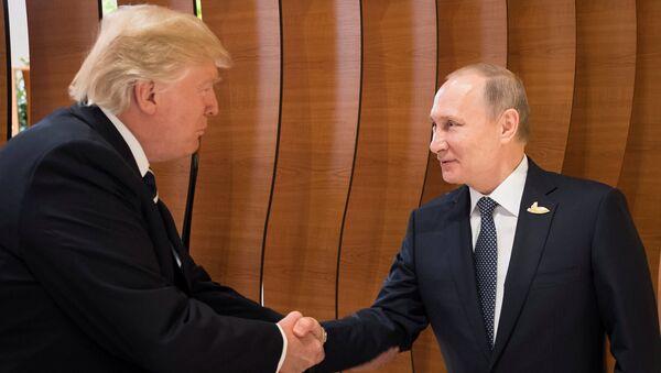 U.S. President Donald Trump and Russia's President Vladimir Putin shake hands during the G20 Summit in Hamburg, Germany in this still image taken from video, July 7, 2017 - Sputnik International