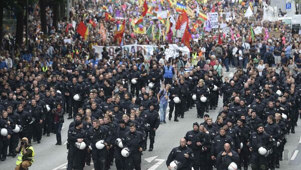 German riot police officers walk in front of protesters during demonstrations at the G20 summit in Hamburg, Germany, July 8, 2017 - Sputnik International