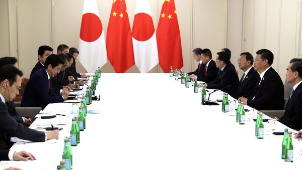In this photo released by China's Xinhua News Agency, Japanese Prime Minister Shinzo Abe, second from left, and Chinese President Xi Jinping, second from right, meet on the sidelines of the G20 summit in Hamburg, Germany, Saturday, July 8, 2017. - Sputnik International