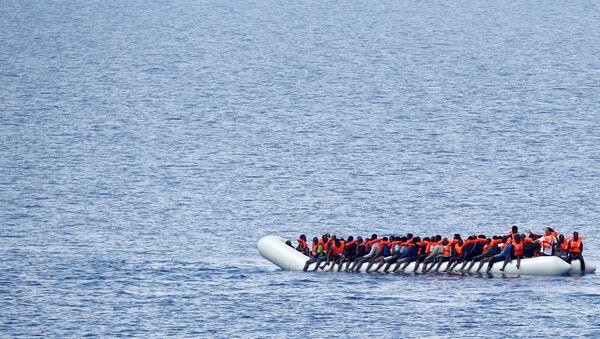Migrants wait to be rescued by Save the Children NGO crew in the Mediterranean sea off Libya coast, June 18, 2017. - Sputnik International