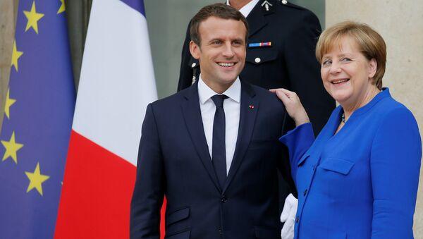 French President Emmanuel Macron (L) accompanies German Chancellor Angela Merkel following a Franco-German joint cabinet meeting at the Elysee Palace in Paris, France, July 13, 2017. - Sputnik International