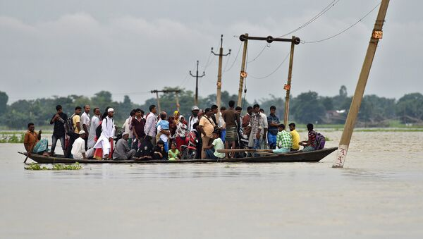 Villagers use a boat to cross a flooded road at Asigarh village in Morigaon district in the northeastern state of Assam, India, July 4, 2017 - Sputnik International