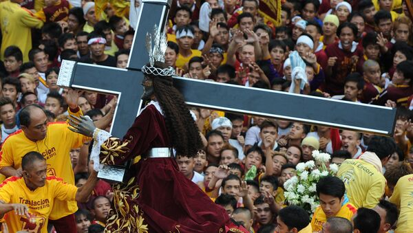 Catholic devotees carry the life-size statue of the Black Nazarene (C) to a carriage during an annual procession in honor of the centuries-old icon of Jesus Christ in Manila on January 9, 2013. - Sputnik International