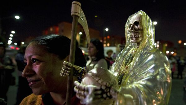 A devotee of the 'Santa Muerte' (Holy Death) holds a image as she prays at the shrine of the goddess at the Iztapalapa shantytown in Mexico City, on February 4, 2011. - Sputnik International