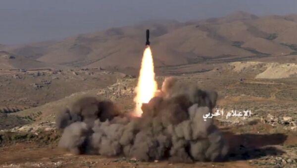 This frame grab from video released on Saturday, July 22, 2017 and provided by the government-controlled Syrian Central Military Media, shows Hezbollah fighters firing a missile at positions of al-Qaida-linked militants in an area on the Lebanon-Syria border - Sputnik International