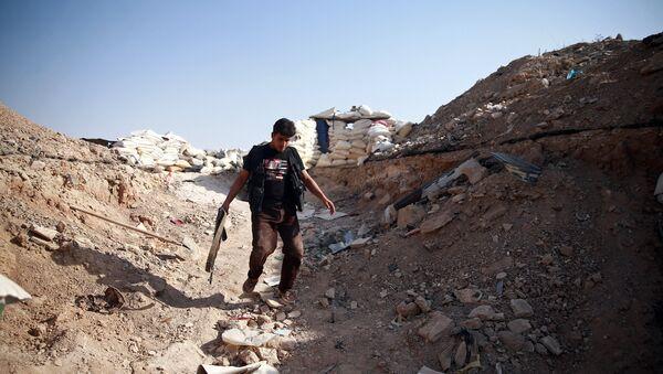 A fighter from Free Syrian Army's Al Rahman legion walks near piled sandbags in Ain Tarma, eastern Damascus suburb of Ghouta, Syria July 17, 2017 - Sputnik International