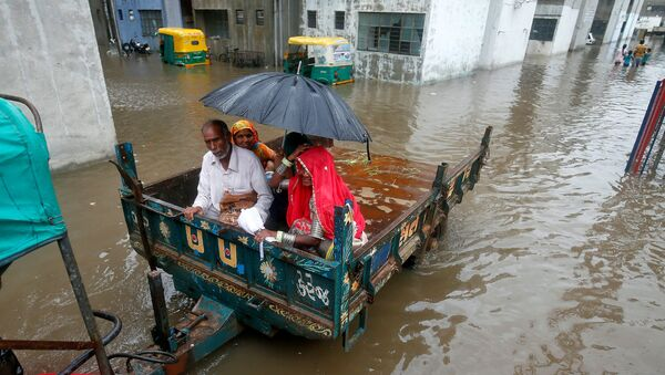 People sit in a tractor trolley as they move out of a flooded neighbourhood after heavy rain in Ahmedabad, India, July 24, 2017.  - Sputnik International
