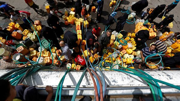 People gather to fill up their jerrycans with drinking water from a charity tanker truck, amid a cholera outbreak, in Sanaa, Yemen, July 12, 2017. - Sputnik International