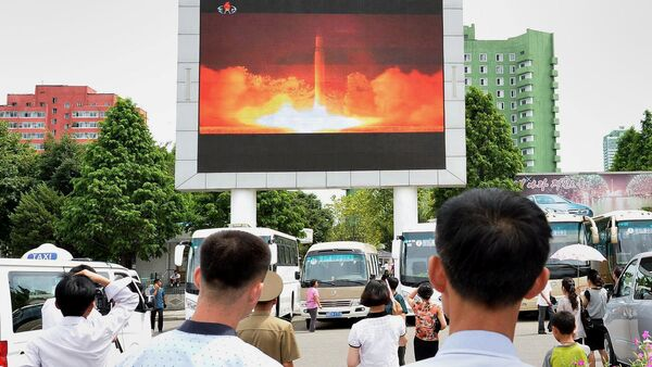 People watch news report showing North Korea's Hwasong-14 missile launch on electronic screen at Pyongyang station, North Korea in this photo taken by Kyodo on July 29, 2017 - Sputnik International