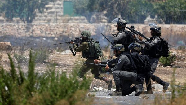 Israeli forces aim their weapons during clashes with Palestinian protesters near the Jewish settlement of Beit El, near the West Bank city of Ramallah July 24, 2017 - Sputnik International