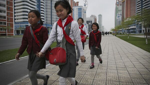 North Korean school girls hold back their laughter at seeing their photograph being taken while walking along Mirae Scientists Street on Wednesday, April 19, 2017, in Pyongyang, North Korea - Sputnik International
