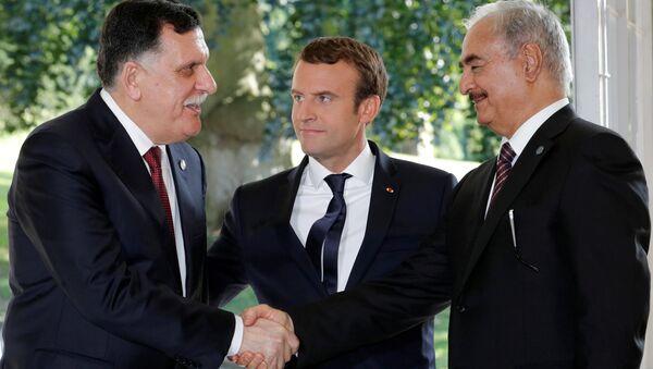 French President Emmanuel Macron stands between Libyan Prime Minister Fayez al-Sarraj (L), and General Khalifa Haftar (R), commander in the Libyan National Army (LNA), who shake hands after talks over a political deal to help end Libya's crisis in La Celle-Saint-Cloud near Paris, France, July 25, 2017 - Sputnik International