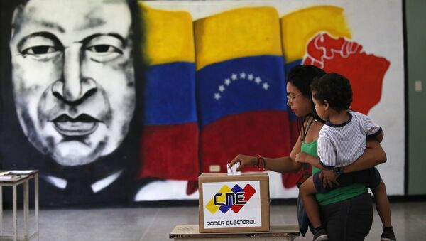 A  woman holds her infant as she casts her vote in front of a mural of the late Venezuelan President Hugo Chavez at a polling station during the Constituent Assembly election in Caracas, Venezuela, July 30, 2017. - Sputnik International