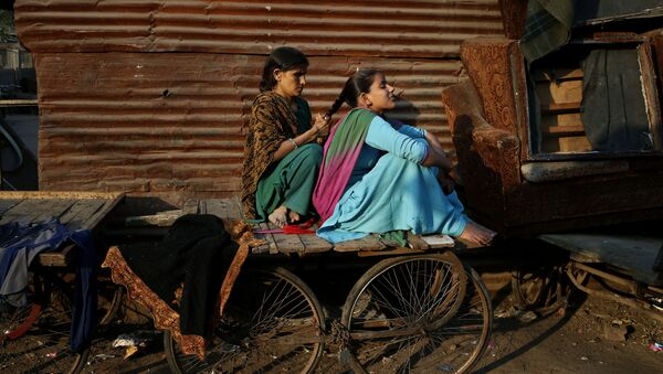 A woman ties the hair of her daughter into a braid as they sit on a cart before evening sets in at a poor neighborhood in New Delhi, India, Thursday, Dec. 5, 2013 - Sputnik International