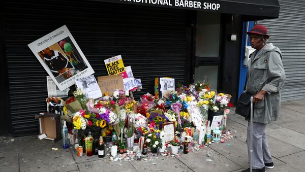 A woman looks at floral tributes laid after the death of Rashan Charles outside a shop in east London - Sputnik International