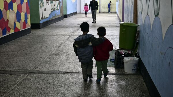 Children walk through a former industrial warehouse at the Oinofyta refugee camp, some 60 km north of Athens, on March 13, 2017 in Oinofyta - Sputnik International