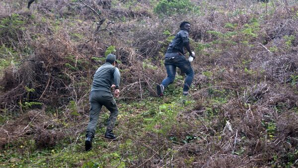 A member of the Moroccan authorities runs after a migrant on February 18, 2017 after he forced his way through a fence between Morocco and the tiny Spanish enclave of Ceuta - Sputnik International