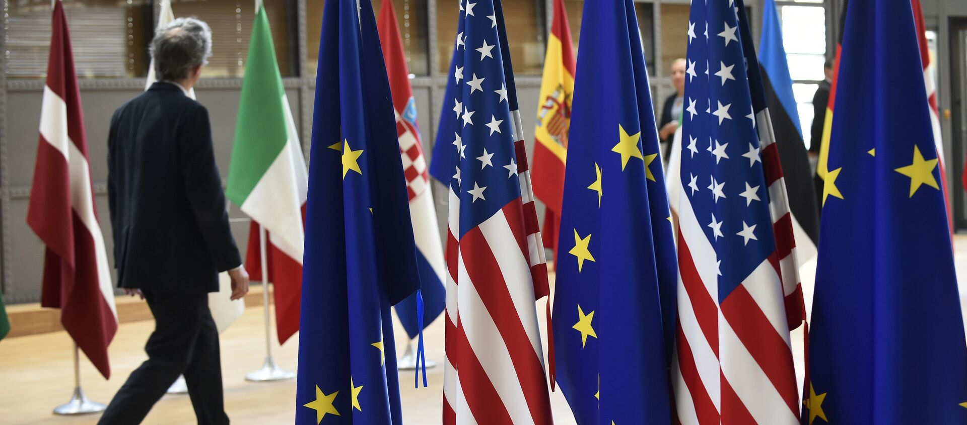A man walks near US and European Union flags at the EU headquarters on May 15, 2017 in Brussels - Sputnik International, 1920, 17.06.2019
