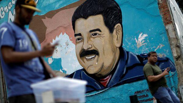 A man walks past a portrait of Venezuela's President Nicolas Maduro in Caracas, Venezuela August 7, 2017. - Sputnik International