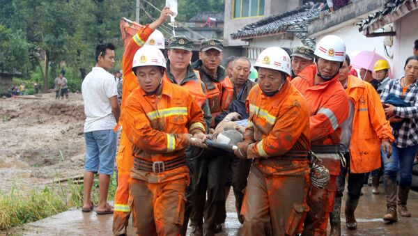 Rescue workers carry an injured villager at the site of a landslide that occurred in Gengdi village, Puge county, Sichuan province, China August 8, 2017 - Sputnik International