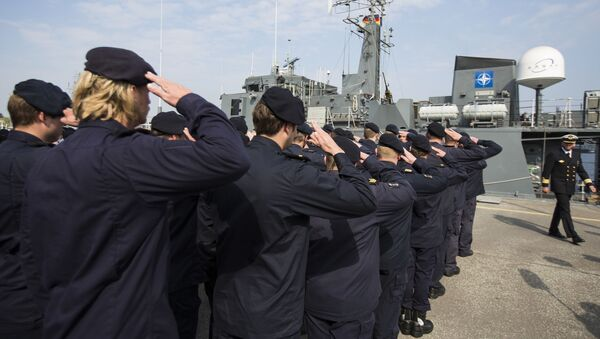 Crew members of Norwegian minesweeper Otra salute after a briefing of NATO Allied Maritime Command Deputy Chief of Staff for Operations, Commodore Arian Minderhoud, right, of the Royal Netherlands Navy before setting sail together in a convoy of five ships of Norway, Belgium, the Netherlands and Estonia from Kiel, Germany, Tuesday, April 22, 2014 - Sputnik International