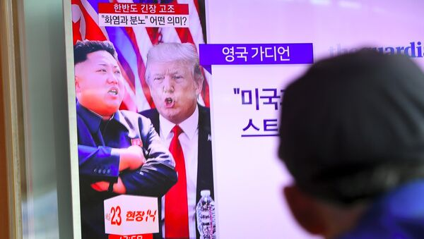 A man watches a television news programme showing US President Donald Trump (C) and North Korean leader Kim Jong-Un (L) at a railway station in Seoul on August 9, 2017 - Sputnik International