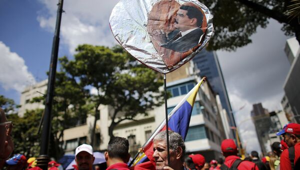 A government supporter holds a heart-shaped placard decorated with an image of Venezuela's Nicolas Maduro during a rally in support of the Constitutional Assembly outside of the National Assembly building in Caracas, Venezuela, Monday, Aug. 7, 2017. - Sputnik International