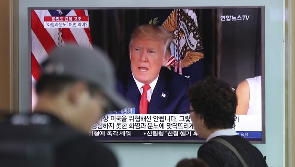 People walk by a TV screen showing a local news program reporting with an image of U.S. President Donald Trump at the Seoul Train Station in Seoul, South Korea, Wednesday, Aug. 9, 2017 - Sputnik International