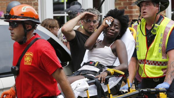 Rescue personnel help an injured woman after a car ran into a large group of protesters after an white nationalist rally in Charlottesville, Va., Saturday, Aug. 12, 2017. - Sputnik International