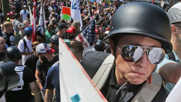 A white nationalist demonstrator with a helmet and shield walks into Lee Park in Charlottesville, Va., Saturday, Aug. 12, 2017. Hundreds of people chanted, threw punches, hurled water bottles and unleashed chemical sprays on each other Saturday after violence erupted at a white nationalist rally in Virginia. - Sputnik International
