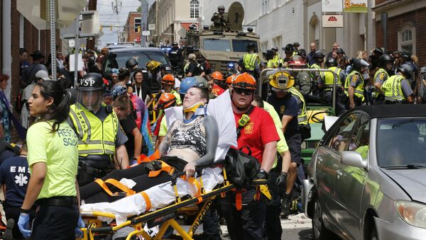 Rescue personnel help injured people after a car ran into a large group of protesters after a white nationalist rally in Charlottesville, Va., Saturday, Aug. 12, 2017. - Sputnik International