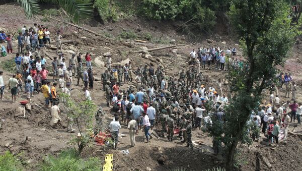 People watch army soldiers and rescue workers recover bodies of landslide victims even as they try to pull out two buses that were covered in mud after a landslide triggered by heavy monsoon rain in Urla village, Himachal Pradesh state, India - Sputnik International