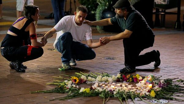 Two people stop to comfort a man as he kneels at a late night vigil to pay his respect for a friend injured in a car attack on counter protesters after a march organized by white nationalists in Charlottesville, Virginia, U.S., August 12, 2017 - Sputnik International