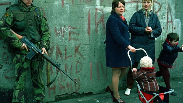 Women and children stand near an armed British military soldier patrols a street in Belfast, Northern Ireland, Feb. 1972. British paratroopers shot 13 demonstrators during a civil rights march on Jan. 30, known as Bloody Sunday. - Sputnik International