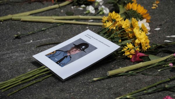 A photo of one of two Virginia state troopers killed in a helicopter crash lies among flowers at a makeshift memorial at the scene of where a car plowed into counter-protesters in Charlottesville, Virginia - Sputnik International