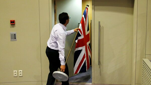 An official carries a Union Jack flag ahead of a news conference by Britain's Secretary of State for Exiting the European Union David Davis and European Union's chief Brexit negotiator Michel Barnier in Brussels, Belgium July 20, 2017 - Sputnik International