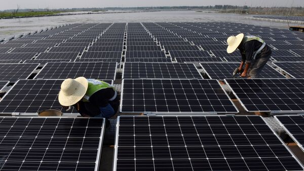 This photo taken on June 7, 2017 shows workers at the world's largest floating solar power plant in a lake in Huainan, in China's central Anhui province - Sputnik International