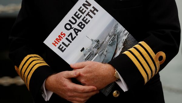 A Naval officer listens to speeches after the arrival of the Royal Navy's new aircraft carrier HMS Queen Elizabeth in Portsmouth, Britain August 16, 2017. - Sputnik International