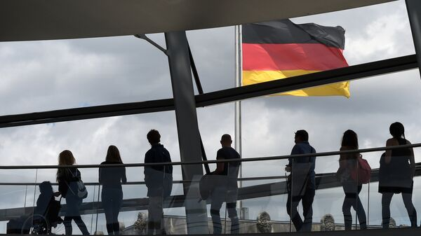 Visitors walk in the glass cupola of the Reichstag building that hosts the German parliament (Bundestag) and look at a German flag in Berlin, Germany, on June 10, 2016. - Sputnik International