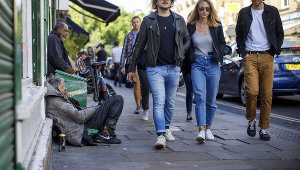 A group of people walks past homeless people on Broadway Market in east London on July 23, 2017 - Sputnik International