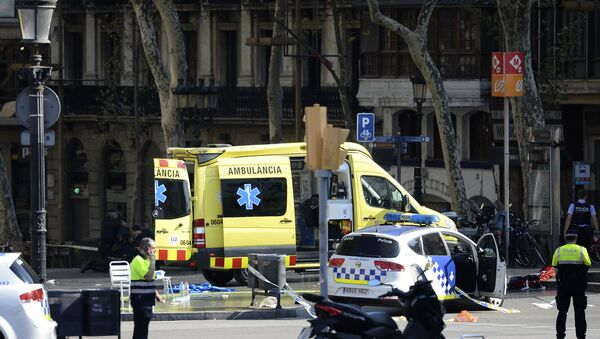 A policemen and a medical staff member stand past police cars and an ambulance in a cordoned off area after a van ploughed into the crowd, injuring several persons on the Rambla in Barcelona on August 17, 2017 - Sputnik International