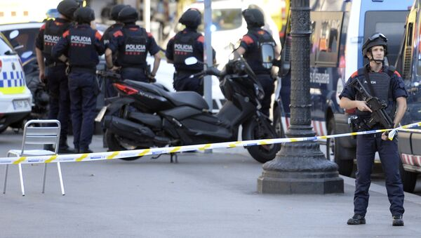 Armed policemen stand in a cordoned off area after a van ploughed into the crowd, injuring several persons on the Rambla in Barcelona on August 17, 2017 - Sputnik International