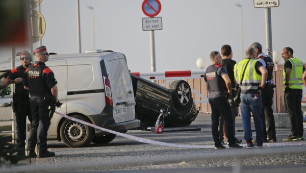 A police officer walks near an overturned car at the spot where terrorists were intercepted by police in Cambrils, Spain, Friday, Aug. 18, 2017 - Sputnik International