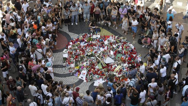 People gather at a memorial tribute of flowers, messages and candles to the victims on Barcelona's historic Las Ramblas promenade on the Joan Miro mosaic, embedded in the pavement where the van stopped after killing at least 13 people in Barcelona , Spain, Friday, Aug. 18, 2017 - Sputnik International