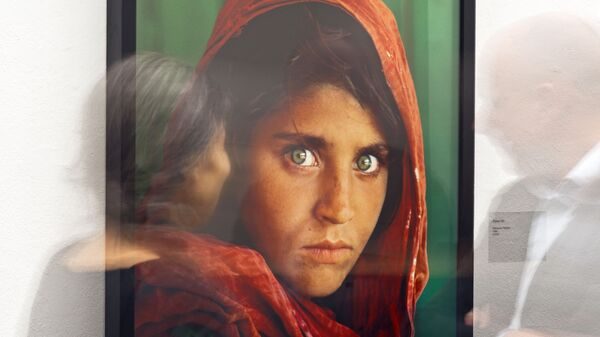 In this picture taken with a long time exposure people walk in front of the photo 'Afghan Girl' (Pakistan, 1984) during the exhibition 'Steve McCurry Retrospective' of US photographer Steve McCurry in the Kunsthalle (Art Hall) in Erfurt, Germany, Wednesday, Feb. 26, 2014.  - Sputnik International